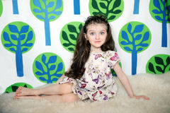 Little girl with long hair in colorful dress sits. On the fur on funny tree background royalty free stock images