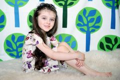 Little girl with long hair in colorful dress sits Stock Photo