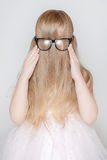 Little girl with long hair covered her face. Little girl playing with her long hair. She's hiding her face and trying to wear glasses Royalty Free Stock Photos