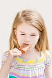 Little girl with long hair eating ice-cream Stock Photo