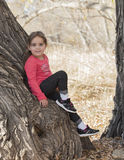 Little Girl with Long Hair Playing Outside Sitting on a Tree Stock Image