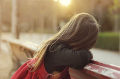Little girl with long hair, rests on a bench in the park, turned Royalty Free Stock Photography