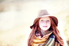 Autumn child portrait. Little girl with long red hair and large blue eyes. Autumn look: brown hat, colorful scarf. Bright sun light in background Royalty Free Stock Images