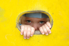 Little girl look out of the hole in painted wall. Stock Images