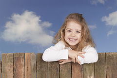 Little girl looking from above a fence, Royalty Free Stock Images