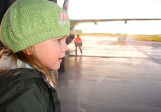 Little girl looking through the airport window. Stock Photos