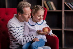 Little girl looking at the apple with her grandfather Stock Photos