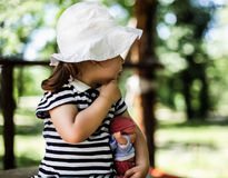 Little girl looking away in nature holding baby doll. Little girl holding doll in her hands Stock Photo