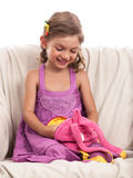 Little girl looking in backpack on sofa isolated Stock Photography