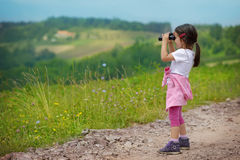 Little girl looking through binoculars outdoor. She is lost. Trying to find a way home Stock Image