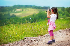 Little girl looking through binoculars outdoor. She is lost. Stock Image