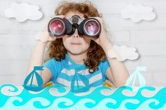 Little girl looking binoculars. Stock Images