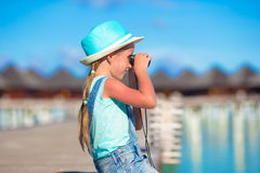 Little girl looking through binoculars in sunny. Day stock photos
