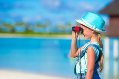 Little girl looking through binoculars in sunny. Day stock image