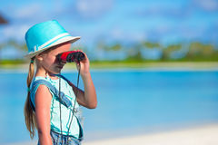 Little girl looking through binoculars in sunny. Day stock photography