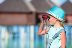 Little girl looking through binoculars in sunny. Day royalty free stock photo