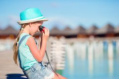 Little girl looking through binoculars in sunny day. During summer vacation sitting naerwater villa on Maldives stock photos