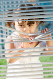 Little girl looking through the blinds Royalty Free Stock Photos