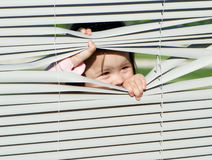 Little girl looking through the blinds Royalty Free Stock Photography