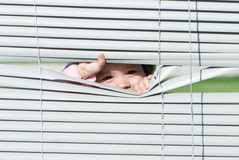 Little girl looking through the blinds Stock Photos
