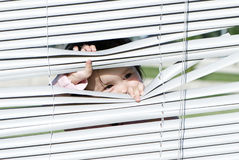 Little girl looking through the blinds Royalty Free Stock Image