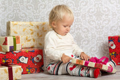 Little girl looking at  box with Christmas present. An adorable baby girl concentrate when holding a wrapped Christmas gift Royalty Free Stock Photo