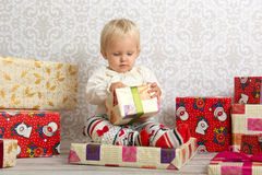 Little girl looking at  box with Christmas present. An adorable baby girl concentrate when holding a wrapped Christmas gift Royalty Free Stock Photos