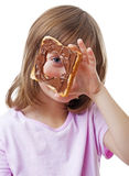 Little girl looking through a  bread with chocolate  butter Royalty Free Stock Image