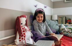 Girl disguised as a butterfly reading with her doll Stock Images