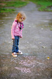 Little girl looking at a chalk drawing Stock Photo