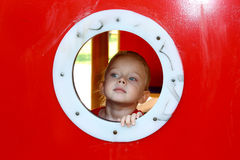 Little girl looking through circle window Royalty Free Stock Photo