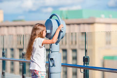 Little girl looking at coin operated binocular on terrace with beautiful view. Cute girl looking at coin operated binocular on terrace with beautiful view Stock Photography