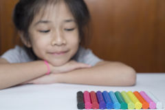 Little girl looking at colorful plasticine. Stock Image