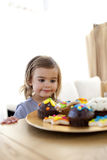 Little girl looking at confectionery at home Stock Photography
