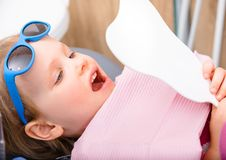 Little girl looking at cured teeth thru the mirror in pediatric dental clinic stock photography