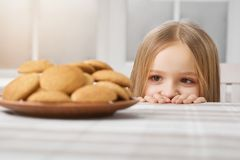 Little girl is looking on delicious cookies and looks hungry. Hungry girl with blonde straight hair and big brown eyes is looking on delicious cookies on white Stock Photo