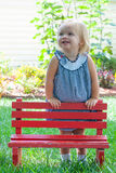 Little Girl Looking into the Distance. Leaning on a Red Bench Stock Photography