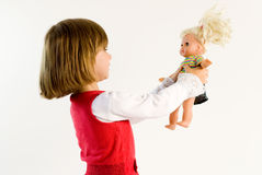 Little girl looking on a doll Stock Photo