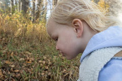 Little girl looking down. Little blonde haired girl looking down Royalty Free Stock Photo