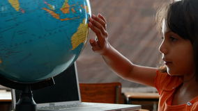 Little girl looking at globe in classroom. In elementary school stock footage