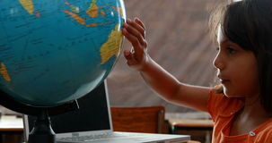 Little girl looking at globe in classroom. In elementary school stock video