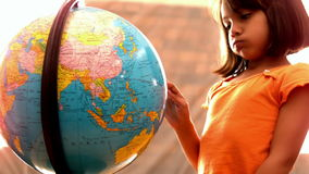 Little girl looking at globe in classroom. In slow motion stock video footage
