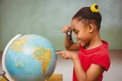 Little girl looking at globe through magnifying glass Stock Photos