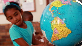 Little girl looking at globe and writing in classroom. In elementary school stock video