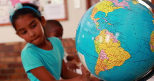 Little girl looking at globe and writing in classroom. In elementary school stock footage
