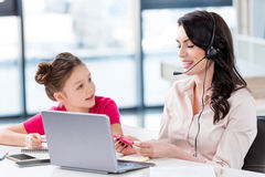 Little girl looking at happy mother in headset working with laptop Royalty Free Stock Photography