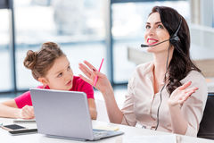 Little girl looking at happy mother in headset working in office Stock Photography