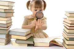 Little girl looking at her nails through magnifier Stock Images