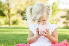 Little Girl Looking into Her Piggy Bank Outdoors Royalty Free Stock Photo