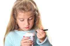 Little girl looking at her yogurt. Shot of a little girl looking at her yogurt Royalty Free Stock Image